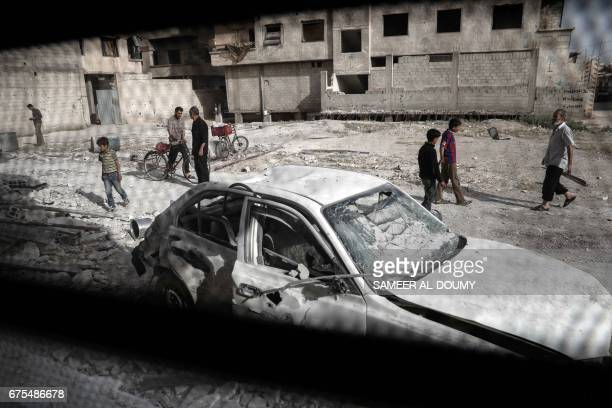 TOPSHOT People inspect a hospital damaged following an air strike a rebelcontrolled town in the eastern Ghouta region on the outskirts of the capital...