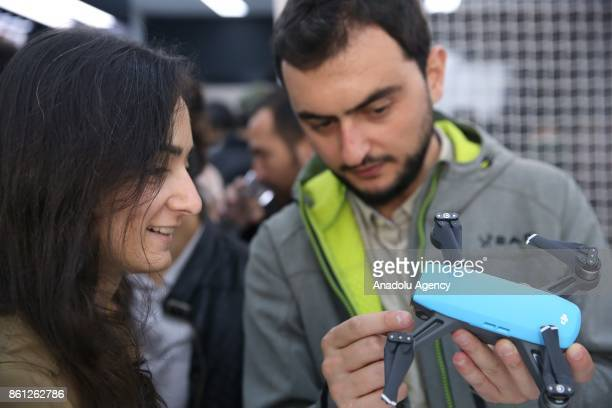 People inspect a miniature drone is seen during the opening of DJI's which is the world's biggest Drone producer company 2nd store in Turkey on...