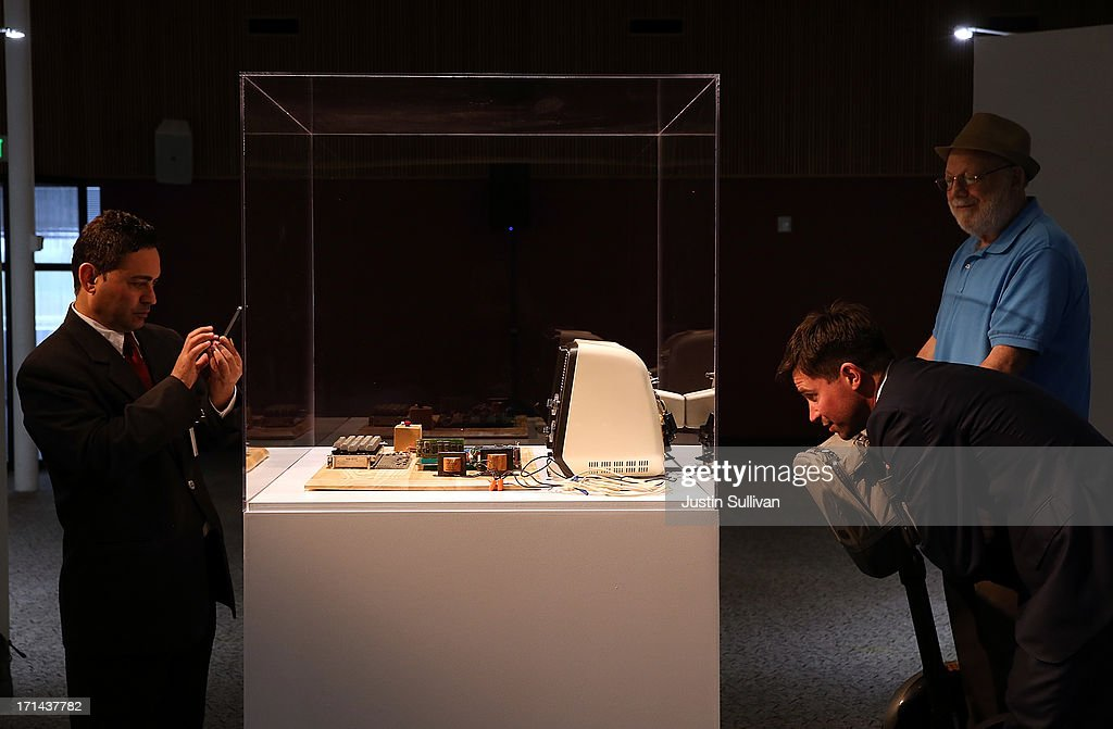 People inspect an Apple-1 computer, built in 1976, that is displayed during the First Bytes: Iconic Technology From the Twentieth Century, an online auction featuring vintage tech products at the Computer History Museum on June 24, 2013 in Mountain View, California. Christie's is auctioning off an original Apple-1 computer owned by Ted Perry as part of its First Bytes: Iconic Technology from the Twentieth Century, an online auction of vintage tech products. The online auction begins today and runs through July 9. The Apple-1 is expected to fetch between $300,000 and $500,000.