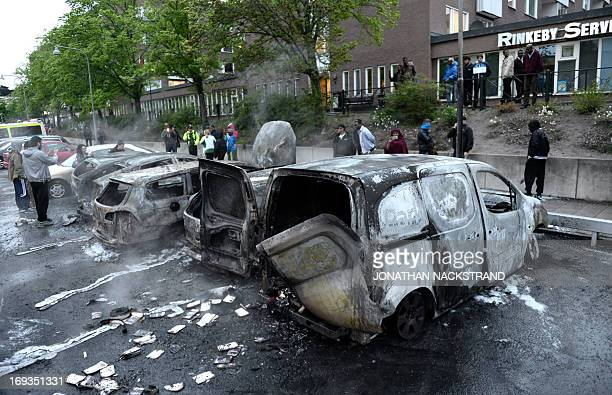People inspect cars gutted by fire in the Stockholm suburb of Rinkeby after youths rioted in several different suburbs around Stockholm Sweden for a...