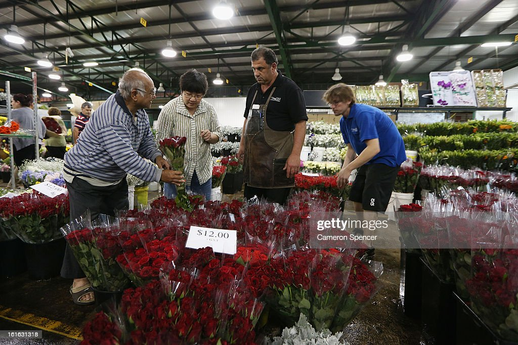 People inspect flowers on display during Valentines Day at Sydney Flower Market on February 14, 2013 in Sydney, Australia. Due to an unusually hot January in Australia an increasing number of roses have been sourced from South America and Africa to ensure Valentines supplies don't run out.