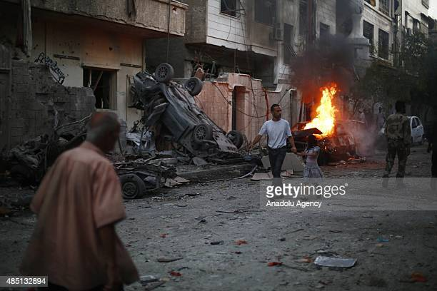 People inspect the attack site and try to recover their lives after Assad regime forces' airstrike staged to residential areas in Douma District of...