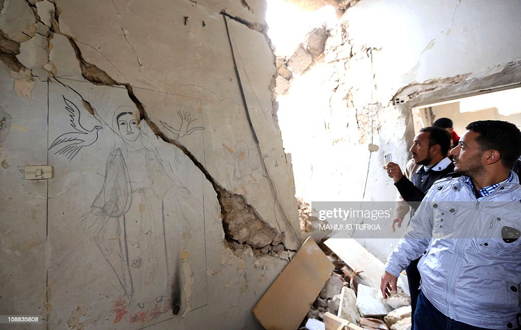 People inspect the Coptic church on December 31, 2012, damaged following an explosion last night in the Mediterranean town of Dafinya, just west of Misrata in which two Egyptians were killed. The stone church was built between 1936 and 1937 during Italian colonial rule and hundreds of Egyptians regularly attended services, the priest said. AFP PHOTO/MAHMUD TURKIA
