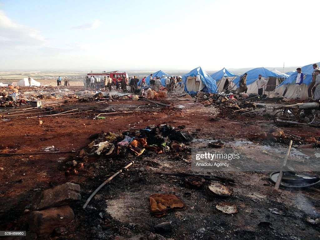 People inspect the damage after a Syrian regime warplane targeted the Kamuna refugee camp near the Syrian town of Sarmada town in the Idlib province after Syrian regime warplane targeted the camp on May 05, 2016. Eight people were killed and another 30 injured when a regime warplane targeted the Kamuna refugee camp.