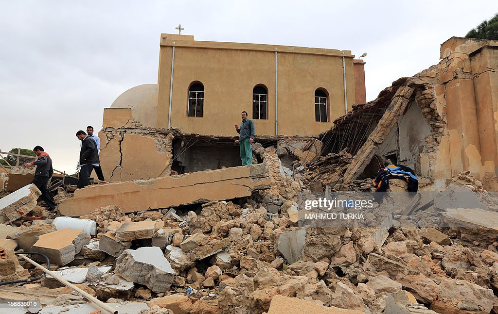 People inspect the destroyed side room of the Coptic church on December 31, 2012, damaged following an explosion last night in the Mediterranean town of Dafinya, just west of Misrata in which two Egyptians were killed. The stone church was built between 1936 and 1937 during Italian colonial rule and hundreds of Egyptians regularly attended services, the priest said.