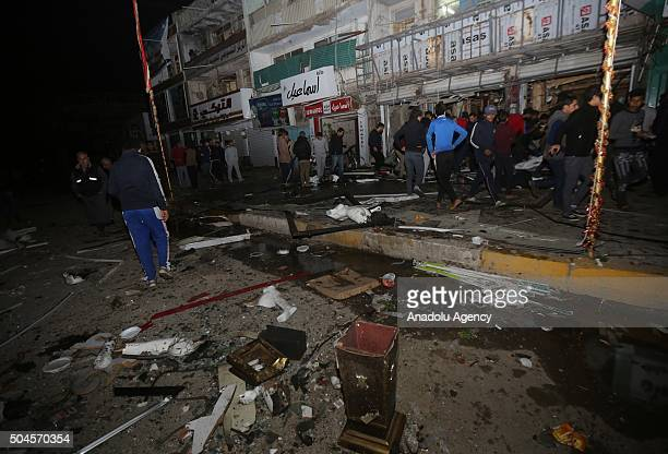 People inspect the explosion site after mulitple suicide bombing attack staged to the AlJawhara Market in AlJadeeda Neighborhood of Baghdad Iraq on...