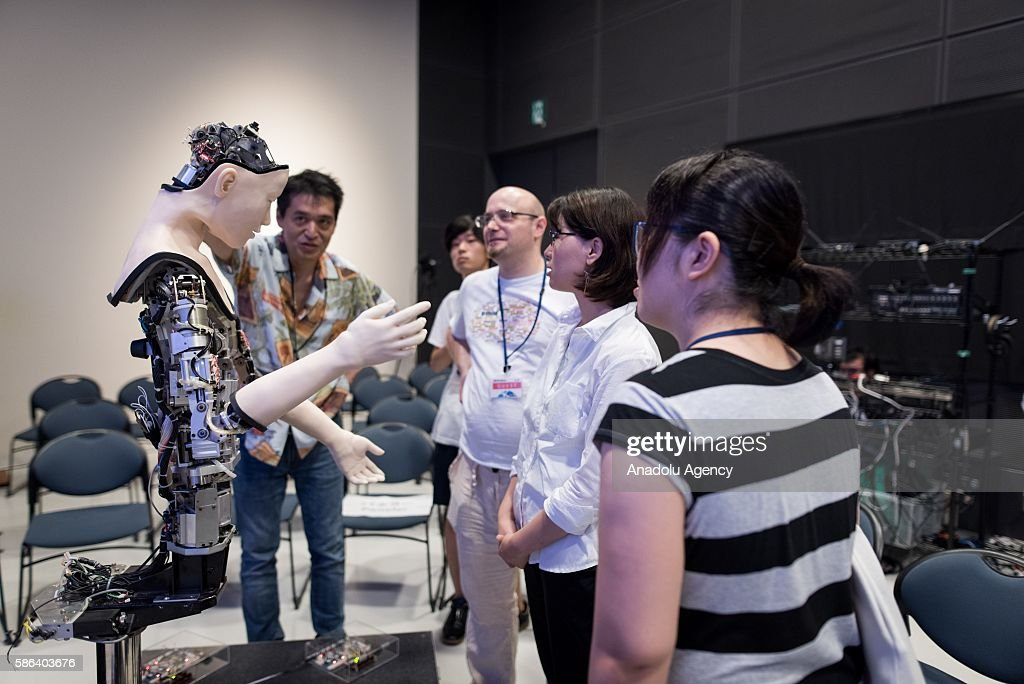 People inspect the humanoid robot called Alter designed by scientists in Japan during the exhibition at the National Museum of Emerging Science and...
