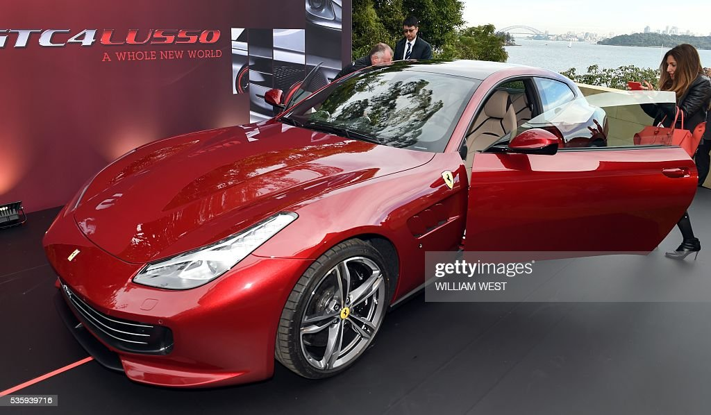 People inspect the new Ferrari GTC4Lusso during the car's Australasian launch in Sydney on May 31, 2016. WEST