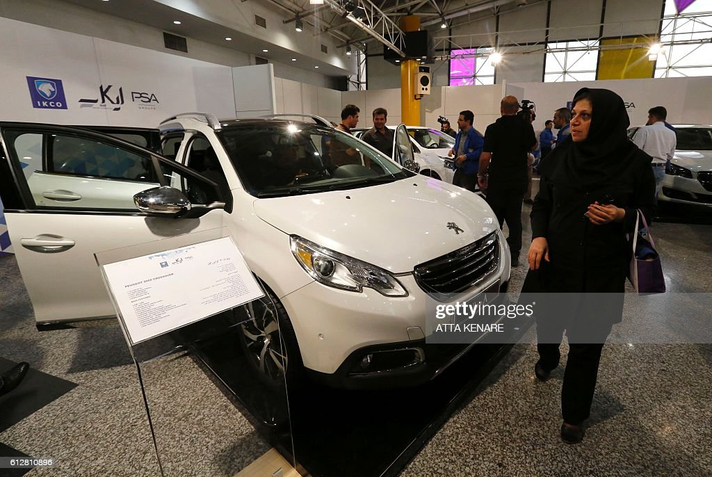 people inspect the new peugeot 2008 car as they visit the iran