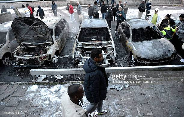 People inspect the scene where cars stand gutted by fire in the Stockholm suburb of Rinkeby after youths rioted in several different suburbs around...