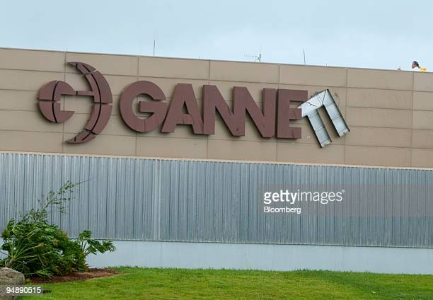 People inspect the sign on Gannett's newspaper building Florida Today near Melbourne Florida September 5 2004 after being hit by Hurricane Frances