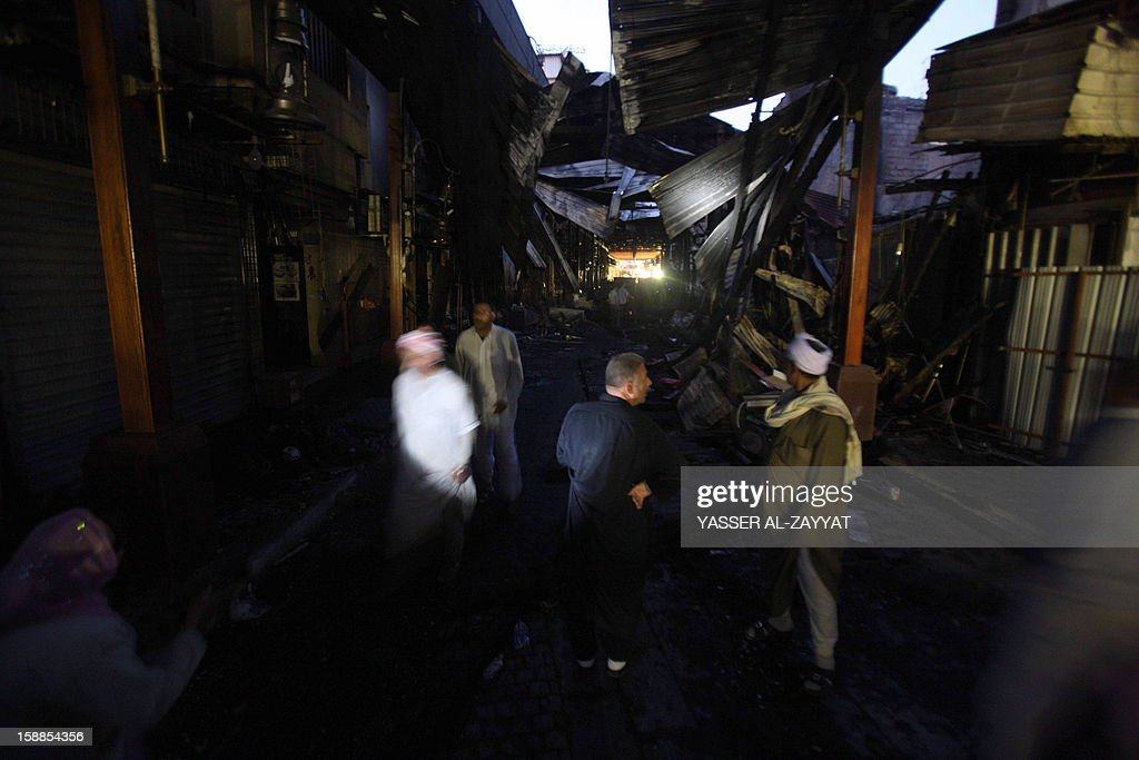 People inspect the site of a fire in Kuwait City's Mubarakiya Market, on January 1, 2013. A major fire broke out in the morning hours at the 'Souk Al-Hareem' (women's market) side of the historical place, ravaging more than 35 shops and destroying an old four-story building. AFP PHOTO / YASSER AL-ZAYYAT