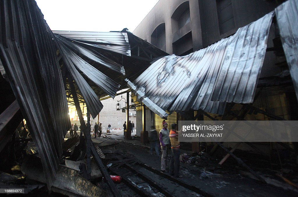 People inspect the site of a fire in Kuwait City's Mubarakiya Market, on January 1, 2013. A major fire broke out in the morning hours at the 'Souk Al-Hareem' (women's market) side of the historical place, ravaging more than 35 shops and destroying an old four-story building.
