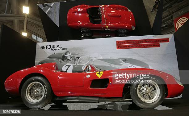 People install a 1957 Ferrari 335S Spider Scaglietti car avalued at more than 32 millions of euros on February 2 2016 at the Artcurial stand during...