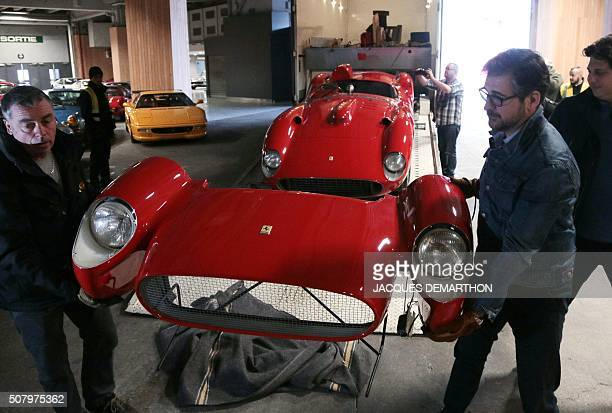 People install a 1957 Ferrari 335S Spider Scaglietti car valued at more than 32 millions of euros on February 2 2016 at the Artcurial stand of the...