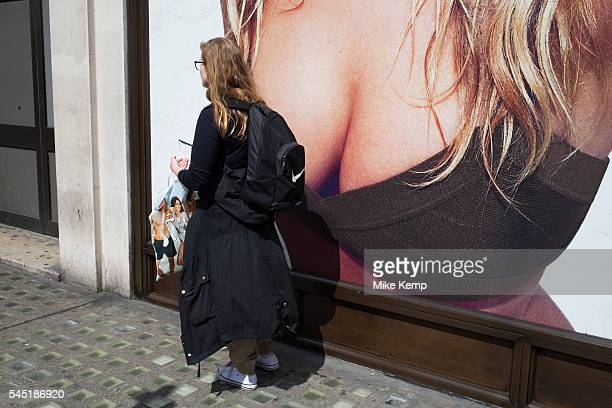People interact with an oversized advertising poster for underwear at HM on Oxford Street in London United Kingdom The advert depicts a young woman...