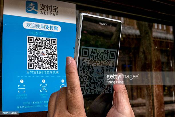 People is scanning the QR code of Alipay outside a shop Alibabas Alipay mobile payments service has a 70% market share in China Since Apple and...