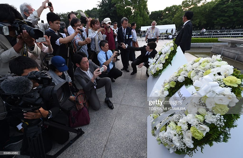 People jam to take pictures of the wreaths placed by US President Barack Obama (R) and Japanese Prime Minister Shinzo Abe (2nd R) in front of the cenotoph in the Peace Momorial park in Hiroshima on May 27, 2016. Obama became the first sitting US leader to visit the site that ushered in the age of nuclear conflict. / AFP / TOSHIFUMI