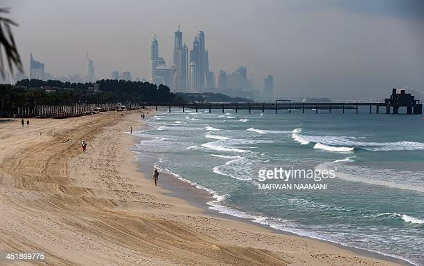 People jog along the Jumierah Beach in the early hours of the morning in Dubai on November 25 2013 The Emirati city is competing with Brazil's Sao...
