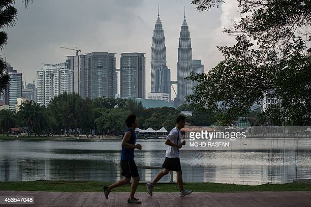 People jog in a park across from Malaysia's landmark Petronas Twin Towers as they loom in the backgrond in Kuala Lumpur on August 13 2014 Malaysian...