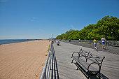 People jogging on boardwalk near white sand beach.