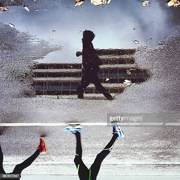 People Jogging, Reflection In Puddle