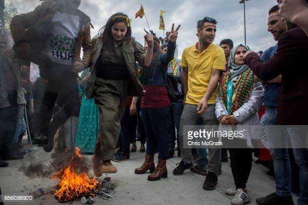 People jump a fire as they celebrate Newroz festivities on March 21 2017 in Istanbul Turkey Newroz is celebrated by Kurdish communities around the...