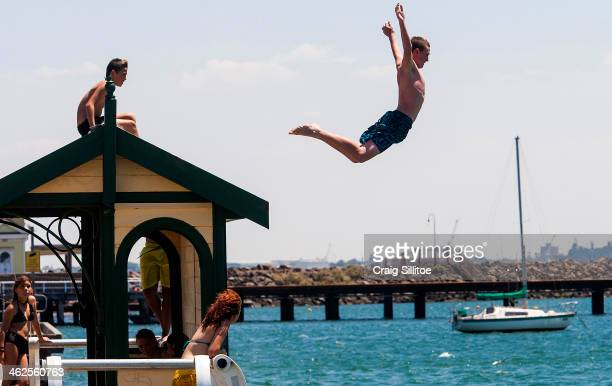 People jump into the sea to keep cool at St Kilda Beach on January 14 2014 in Melbourne Australia Temperatures are expected to reach over 40 degrees...