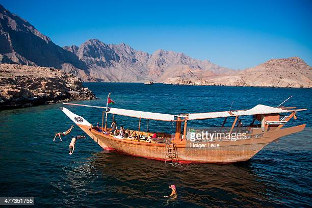 People jump into water from traditional dhow