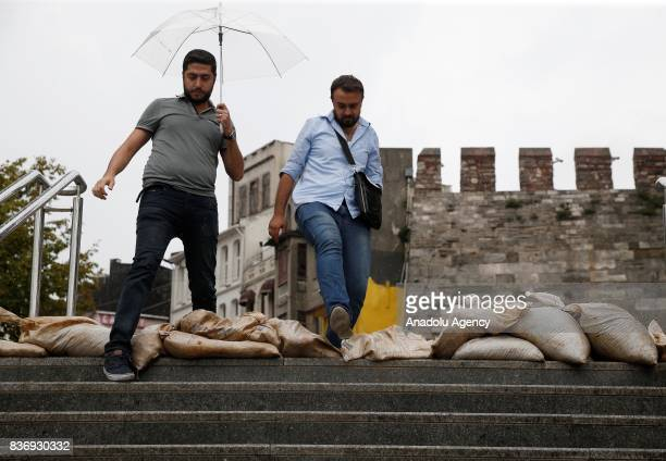 People jump onto the sandbags which were put at the entrance of an underpass as a precaution for the rainfall as the rain starts to become effective...