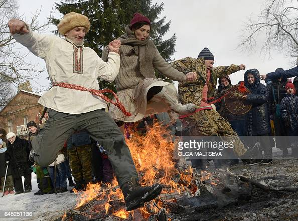 TOPSHOT People jump over a campfire as Russians celebrate Maslenitsa a farewell ceremony to winter in Vsevolozhsk outside Saint Petersburg on...