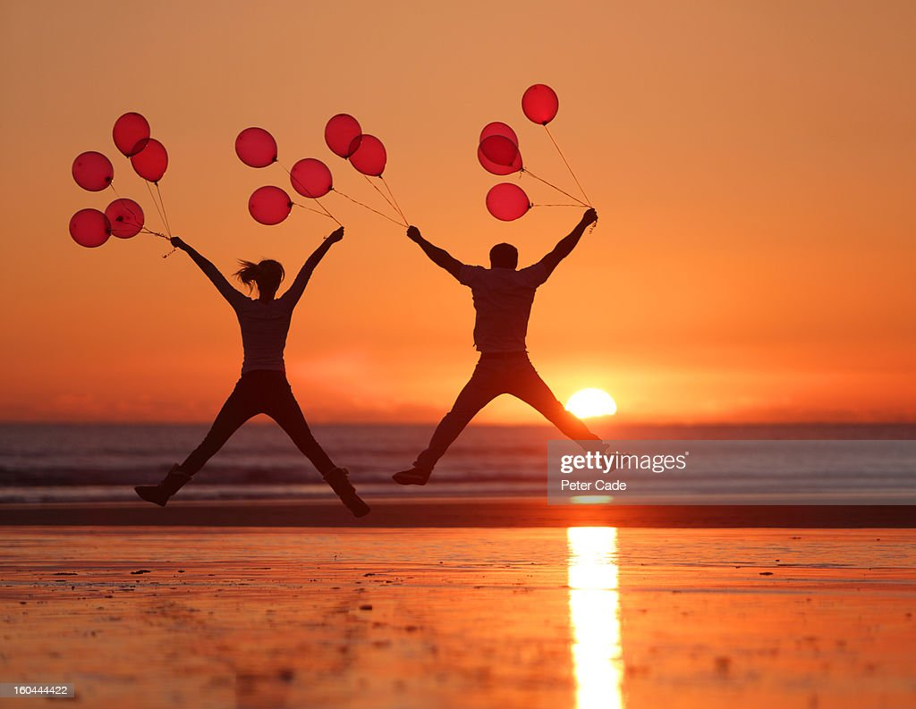People jumping on beach at sunset holding balloons : Stock Photo