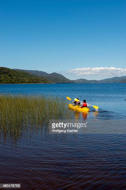 People kayaking on Lake Cucao in Cucao Chiloe National Park on Chiloe Island Chile