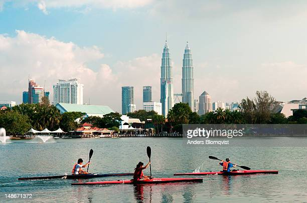 People kayaking on Lake Titiwangsa with Petronas Towers as backdrop.