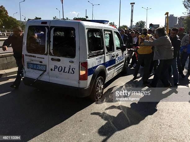 People kick a police vehicle at the site of an explosion close to Ankara's main train station on October 10 2015 in Ankara Turkey A bomb exploded...