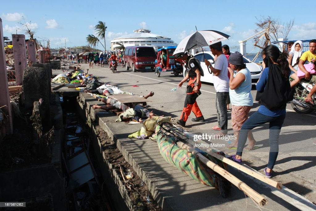 People killed during Typhoon Haiyan are lined up on the side of the road on November 10, 2013 in Tacloban City, Leyte, Philippines. Typhoon Haiyan, packing maximum sustained winds of 195 mph (315 kph), slammed into the southern Philippines and left a trail of destruction in multiple provinces, forcing hundreds of thousands to evacuate and making travel by air and land to hard-hit provinces difficult. Around 10,000 people are feared dead in the strongest typhoon to hit the Philippines this year.