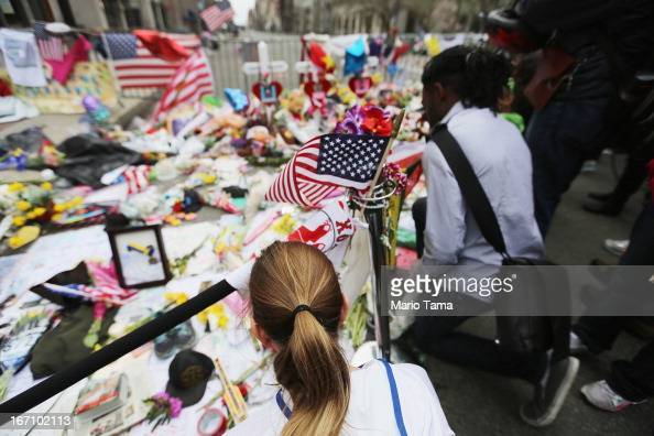 People kneel at a makeshift memorial for victims near the site of the Boston Marathon bombings a day after the second suspect was captured on April...
