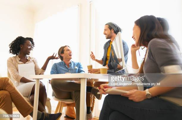 People laughing in meeting at office