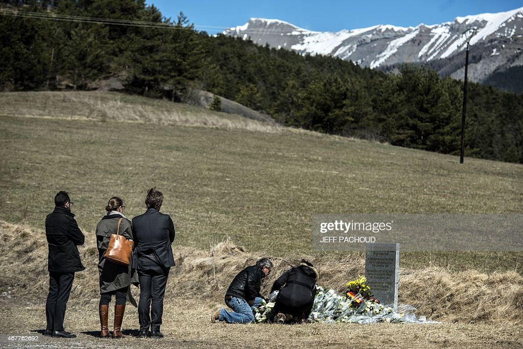 People lay a wreath of flowers as they pay tribute in front of a stele carved in French German Spanish and English in memory of the victims of the...