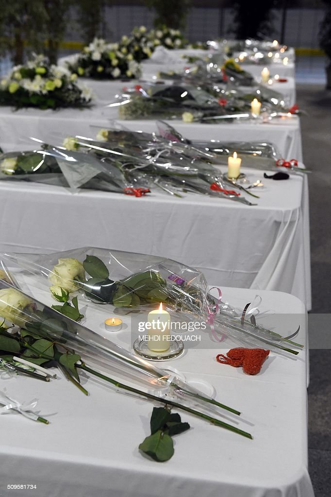People lay candles and flowers on six tables representing coffins in Surgeres, on February 11, 2016, in tribute to the victims of the road accident between a school bus and a truck, killing at least six children. The head-on smash with a lorry carrying rubble came around 7:15 am (0615 GMT) in Rochefort in the western Charente-Maritime region. The school bus was carrying about 17 people, and three children suffered minor injuries in the accident, a police source said. / AFP / MEHDI FEDOUACH