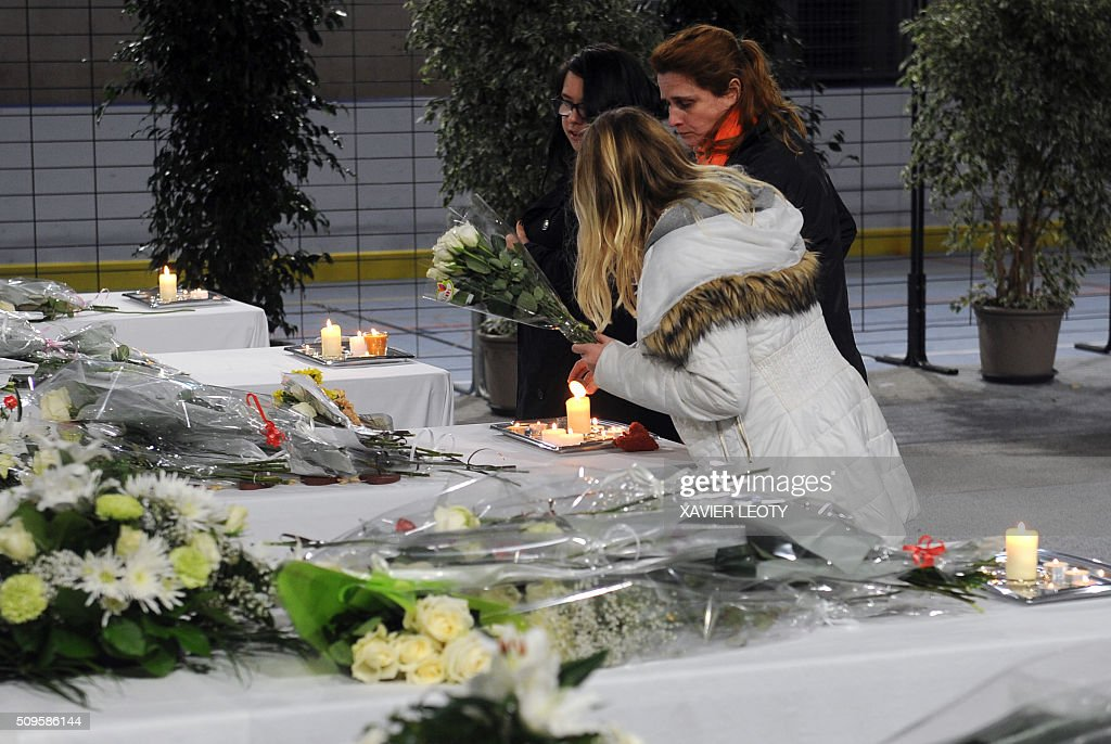People lay candles and flowers on six tables representing coffins in Rochefort, on February 11, 2016, in tribute to the victims of the road accident between a school bus and a truck, killing at least six children. The head-on smash with a lorry carrying rubble came around 7:15 am (0615 GMT) in Rochefort in the western Charente-Maritime region. The school bus was carrying about 17 people, and three children suffered minor injuries in the accident, a police source said. / AFP / XAVIER LEOTY