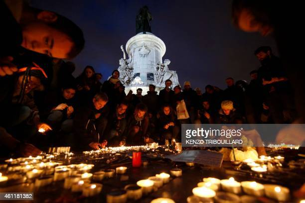 People lay candles during a gathering on the Place de Republique in Paris on January 8 as a tribute to the 12 people killed by two gunmen at the...