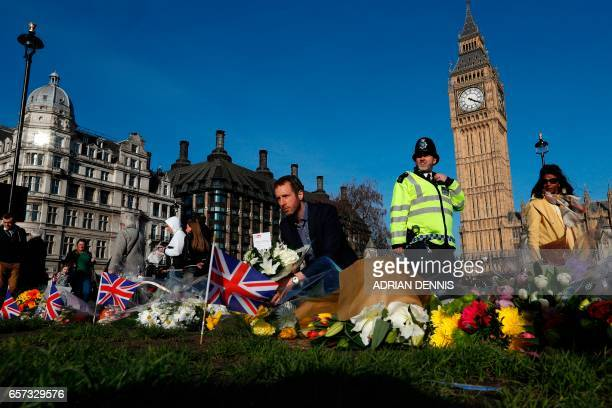 People lay floral tributes to the victims of the March 22 terror attack in Parliament Square outside the Houses of Parliament in central London on...