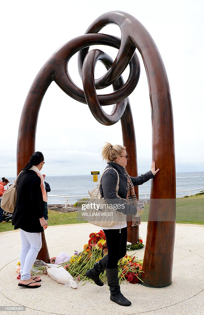 People lay flowers after a ceremony to commemorate the 10th anniversary of the 2002 Bali attacks, at a memorial dedicated to Australians killed in the attacks, at Coogee Beach in Sydney on October 12, 2012. Survivors and relatives of the dead flocked to emotional Bali bombing ceremonies across Australia on October 12, with Foreign Minister Bob Carr praising the nation's mature response to the atrocity. AFP PHOTO/William WEST