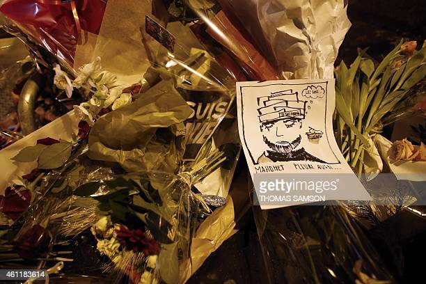 People lay flowers and a cartoon reading 'Mohamet cries too' outside the offices of the French satirical newspaper Charlie Hebdo in Paris on January...