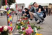 People lay flowers and candles near the crime scene outside the OEZ shopping center the day after a shooting spree left nine victims dead on July 23...
