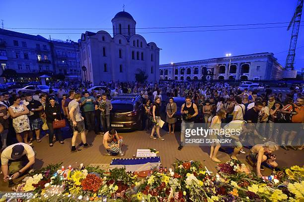 People lay flowers and light candles in front of the Embassy of the Netherlands in Kiev on July 17 to commemorate passengers of Malaysian Airlines...