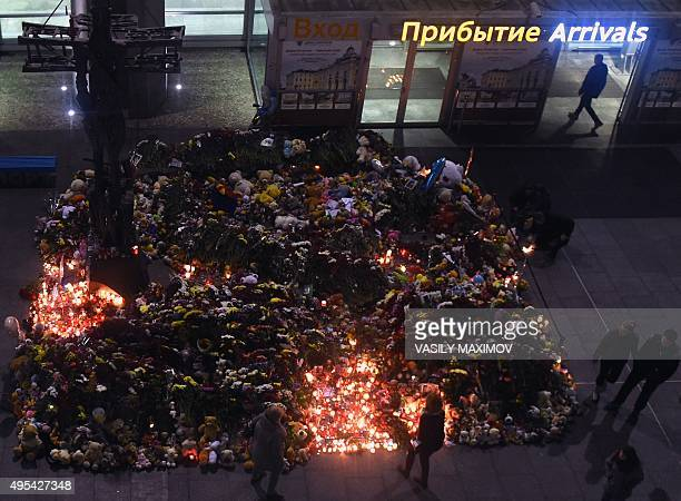 People lay flowers and light candles outside Pulkovo International Airport in St Petersburg on November 2 in memory of the victims of a jetliner...