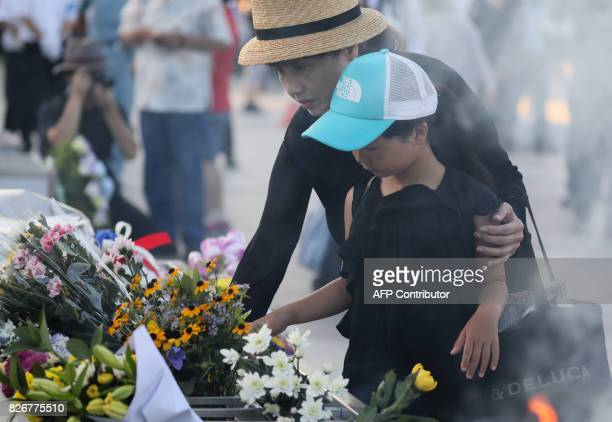 People lay flowers and offer prayers early morning prior to the 72nd anniversary memorial service for the atomic bomb victims at the Peace Memorial...