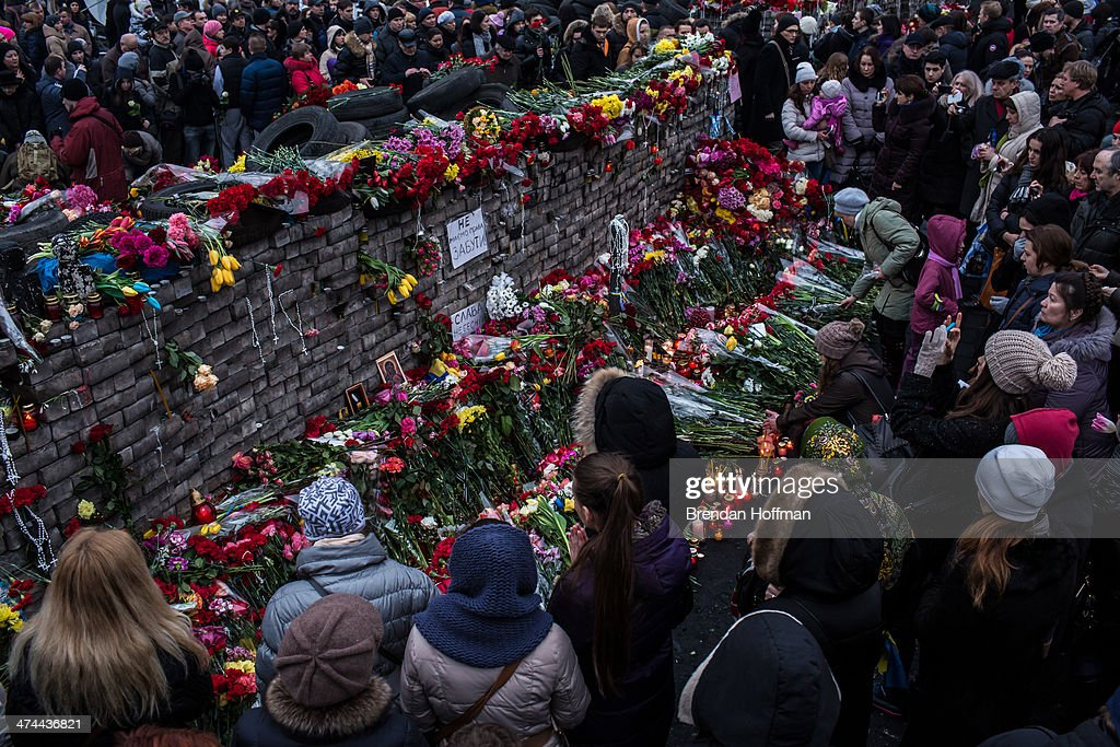 People lay flowers and pay their respects at a memorial for anti-government protesters killed in clashes with police in Independence Square on February 23, 2014 in Kiev, Ukraine. After a chaotic and violent week, Viktor Yanukovych has been ousted as President as the Ukrainian parliament moves forward with scheduling new elections and establishing a caretaker government.